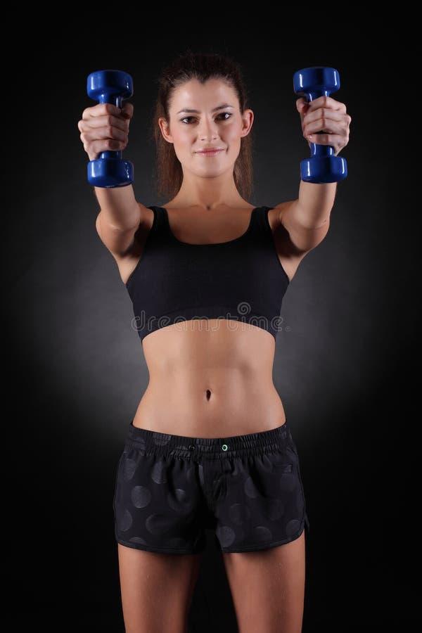 Mujer deportiva hermosa que se resuelve con pesas de gimnasia foto de archivo