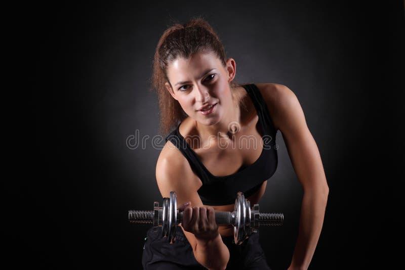 Mujer deportiva hermosa que se resuelve con pesas de gimnasia fotografía de archivo