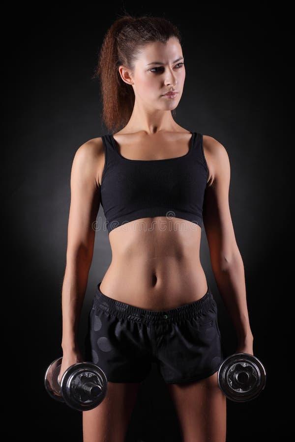 Mujer deportiva hermosa que se resuelve con pesas de gimnasia fotografía de archivo libre de regalías