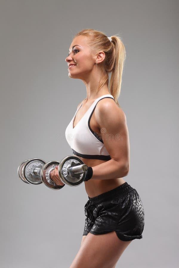 Mujer deportiva hermosa que se resuelve con pesas de gimnasia imágenes de archivo libres de regalías