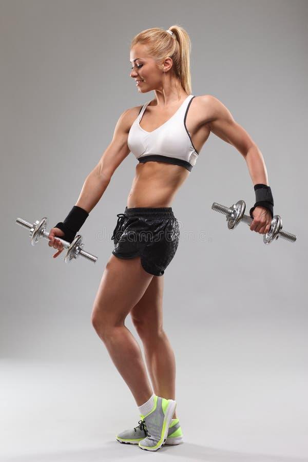 Mujer deportiva hermosa que se resuelve con pesas de gimnasia foto de archivo libre de regalías