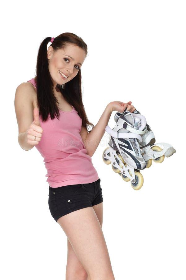Mujer deportiva joven con los rollerskates imagen de archivo