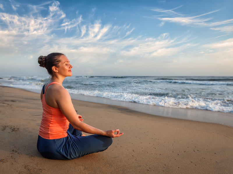 Mujer deportiva joven del ajuste que hace oudoors de la yoga en la playa foto de archivo