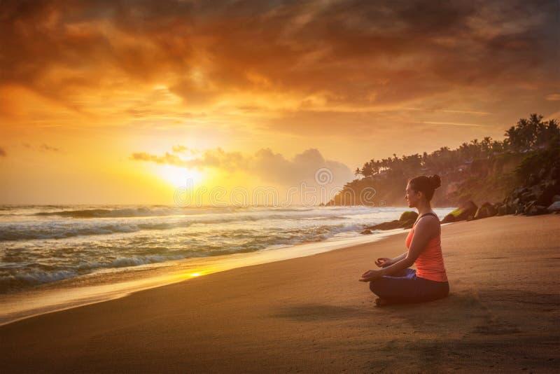 Mujer deportiva joven del ajuste que hace oudoors de la yoga en la playa fotos de archivo