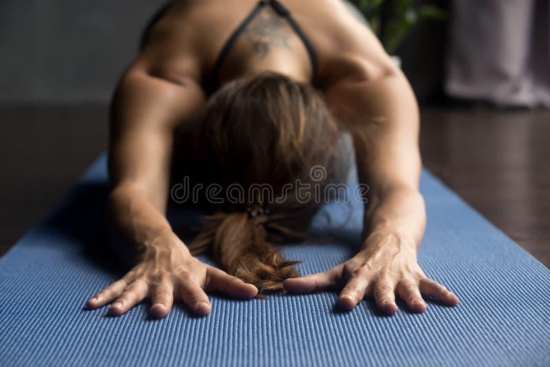 Mujer deportiva joven en la actitud de Balasana, cierre encima de la visión fotos de archivo