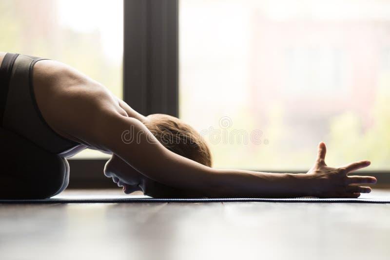 Mujer deportiva joven en la actitud de Balasana, cierre para arriba foto de archivo libre de regalías