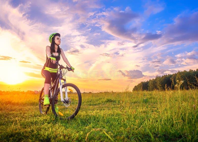 Mujer deportiva joven en la puesta del sol en una bicicleta Muchacha deportiva en la bici parada para disfrutar del momento en la fotos de archivo libres de regalías