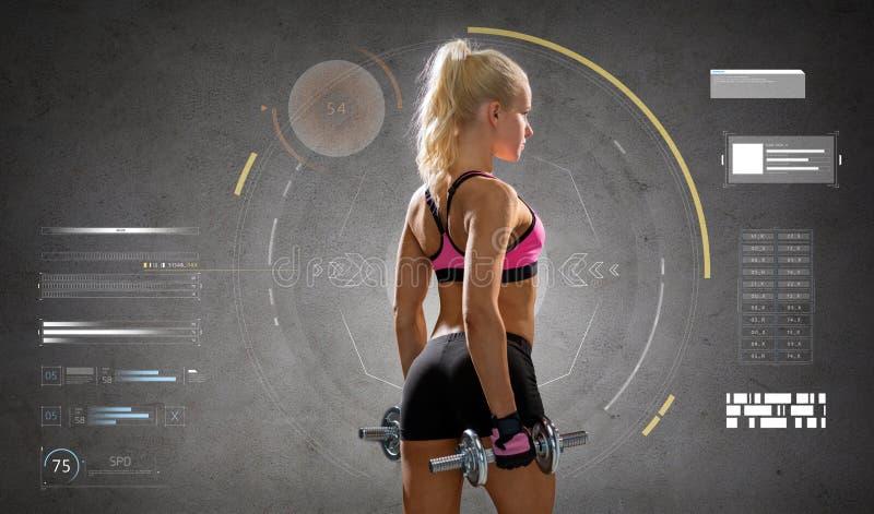 Mujer deportiva joven feliz que ejercita con pesas de gimnasia imagen de archivo