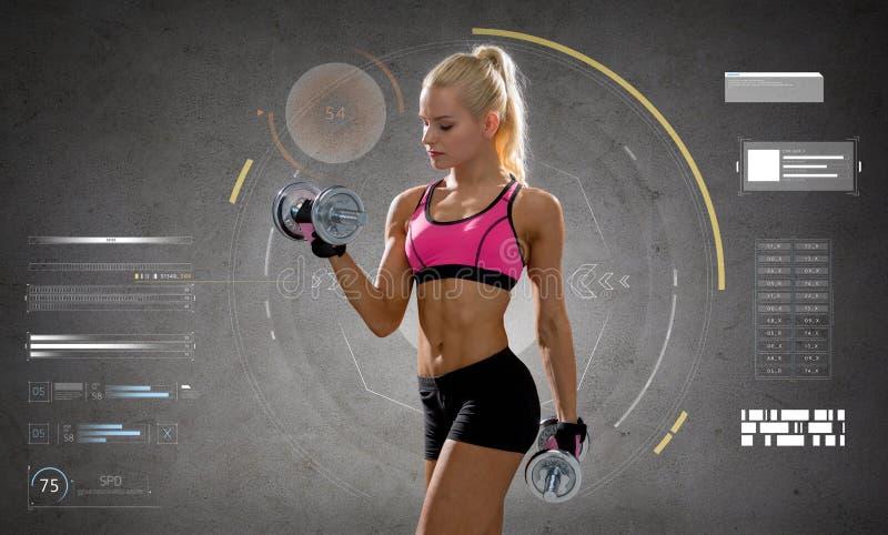 Mujer deportiva joven feliz que ejercita con pesas de gimnasia imagenes de archivo