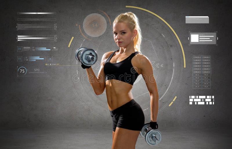 Mujer deportiva joven feliz que ejercita con pesas de gimnasia fotos de archivo