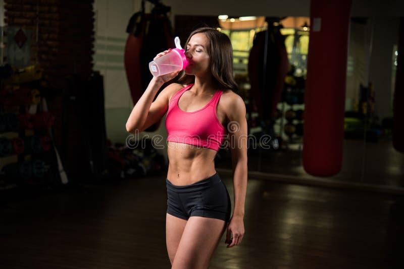 Mujer deportiva joven que bebe de una coctelera imagen de archivo libre de regalías