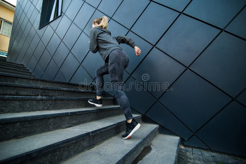 Mujer deportiva joven que corre arriba en las escaleras de la ciudad al aire libre imágenes de archivo libres de regalías
