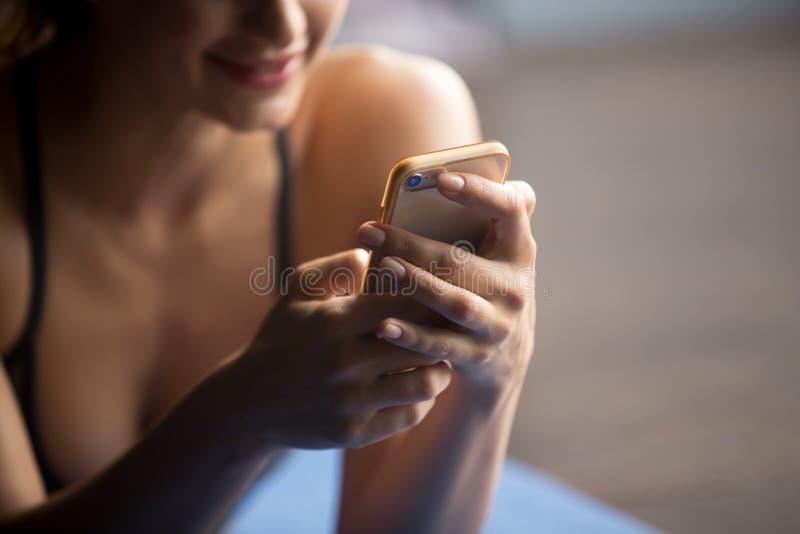 Mujer deportiva joven que detiene el smartphone, cierre fotos de archivo libres de regalías