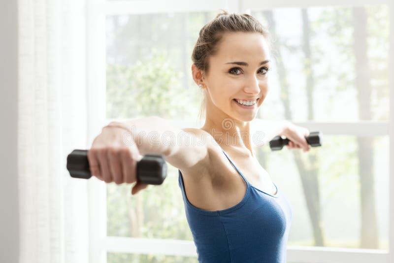 Mujer deportiva joven que ejercita con pesas de gimnasia en casa imagen de archivo libre de regalías