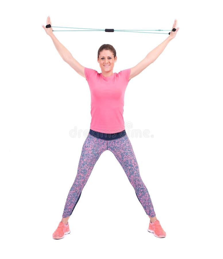 Mujer deportiva joven que ejercita con una cuerda de la resistencia imagen de archivo