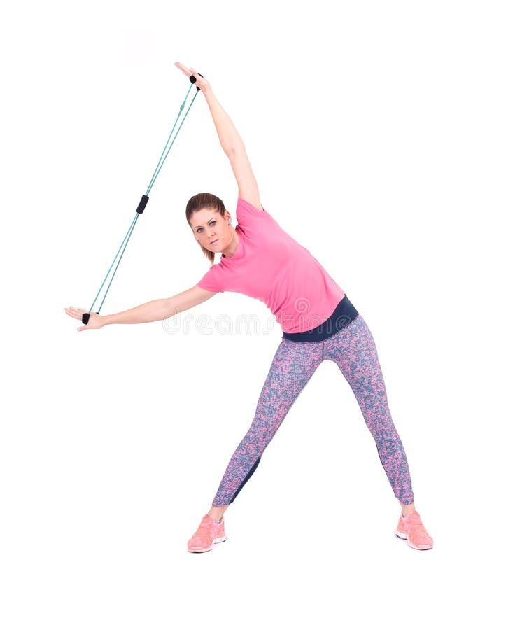 Mujer deportiva joven que ejercita con una cuerda de la resistencia fotografía de archivo