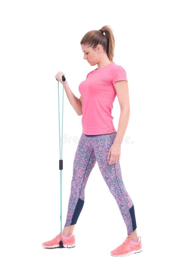Mujer deportiva joven que ejercita con una cuerda de la resistencia imagen de archivo libre de regalías