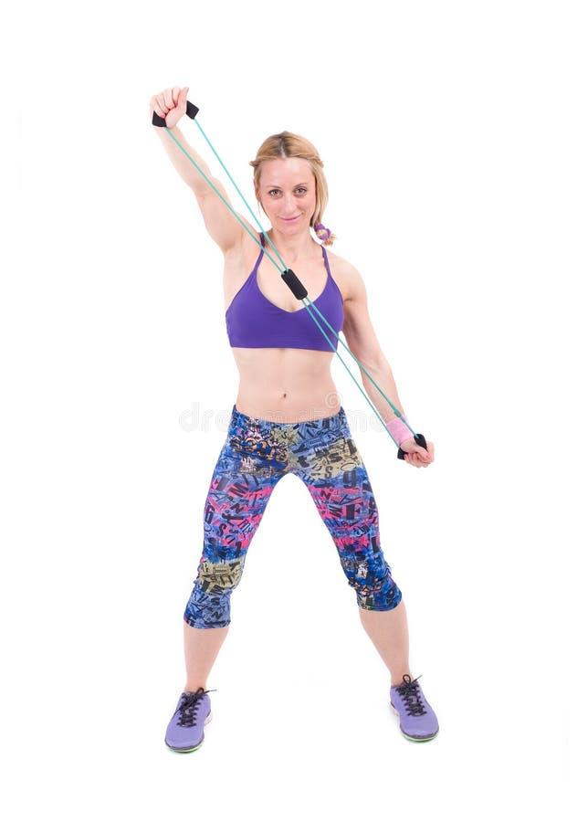 Mujer deportiva joven que ejercita con una cuerda de la resistencia fotografía de archivo libre de regalías