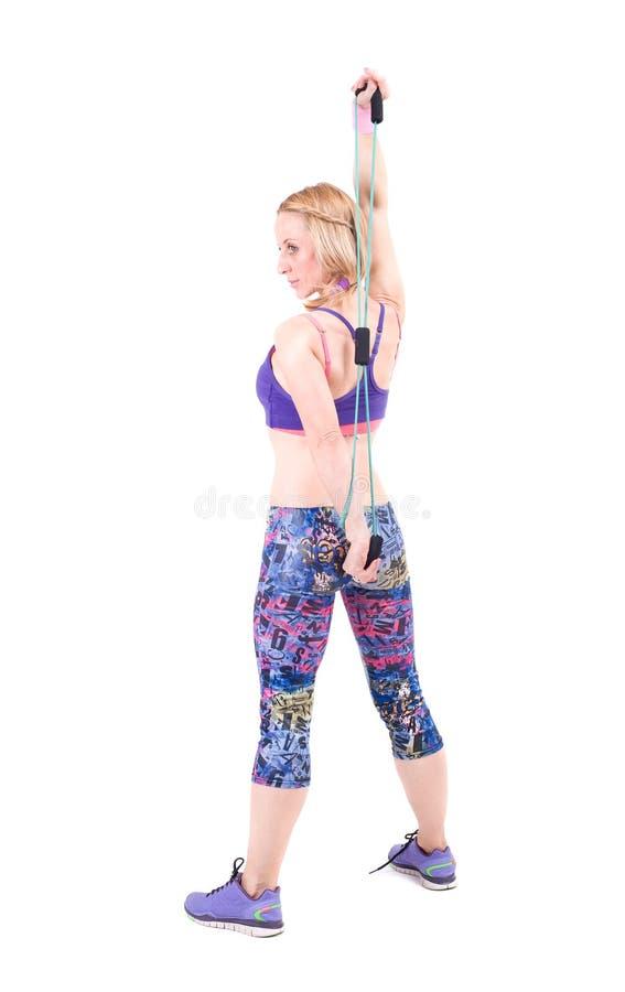 Mujer deportiva joven que ejercita con una cuerda de la resistencia fotos de archivo