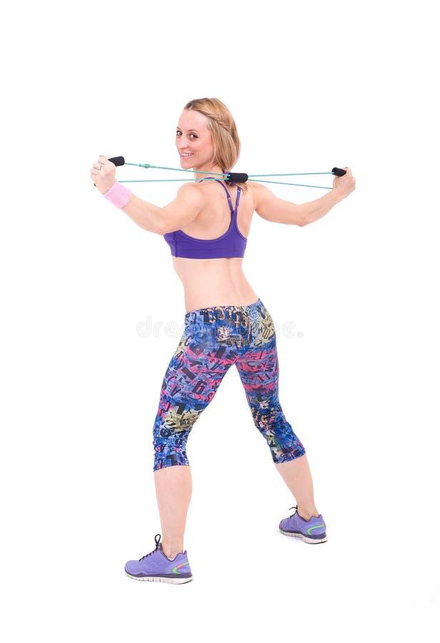 Mujer deportiva joven que ejercita con una cuerda de la resistencia fotos de archivo libres de regalías