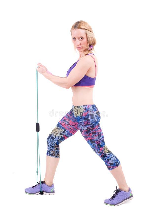 Mujer deportiva joven que ejercita con una cuerda de la resistencia foto de archivo