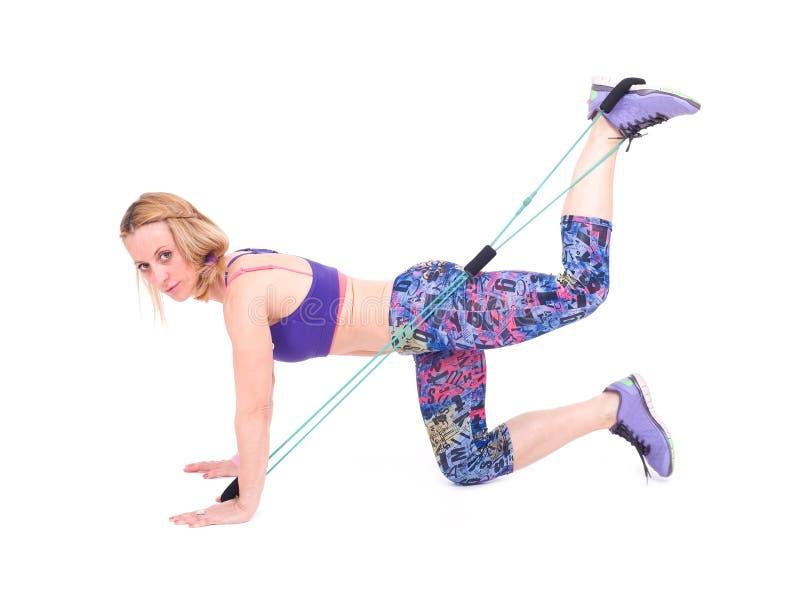 Mujer deportiva joven que ejercita con una cuerda de la resistencia foto de archivo libre de regalías