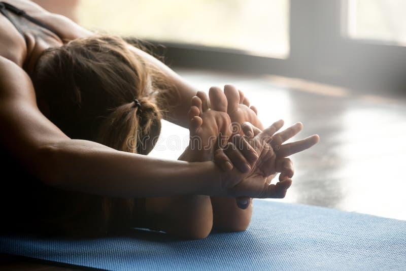 Mujer deportiva joven que hace el ejercicio del paschimottanasana, cierre para arriba imagen de archivo