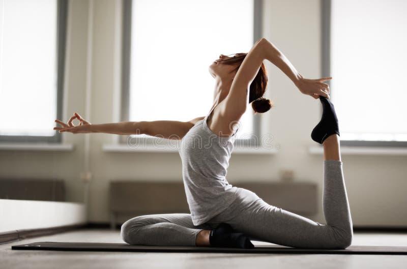 Mujer deportiva joven que hace la yoga que estira el ejercicio que se sienta en gimnasio cerca de ventanas brillantes imagen de archivo