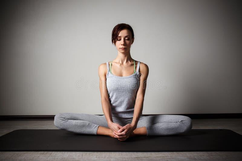 Mujer deportiva joven que hace la yoga que estira el ejercicio que se sienta en gimnasio cerca de ventanas brillantes foto de archivo