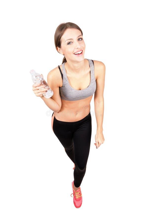 Mujer deportiva joven que sonríe en la cámara que sostiene la botella de agua imagenes de archivo