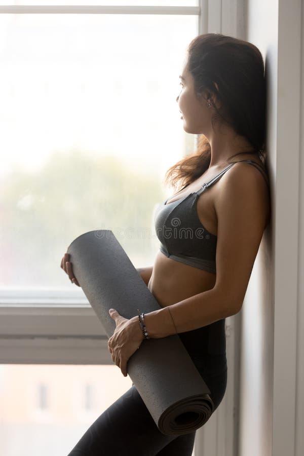 Mujer deportiva joven que sostiene la estera de la aptitud, instructor de la yoga imágenes de archivo libres de regalías