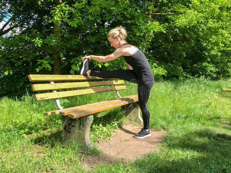 Mujer deportiva muscular limbering para arriba en un parque foto de archivo