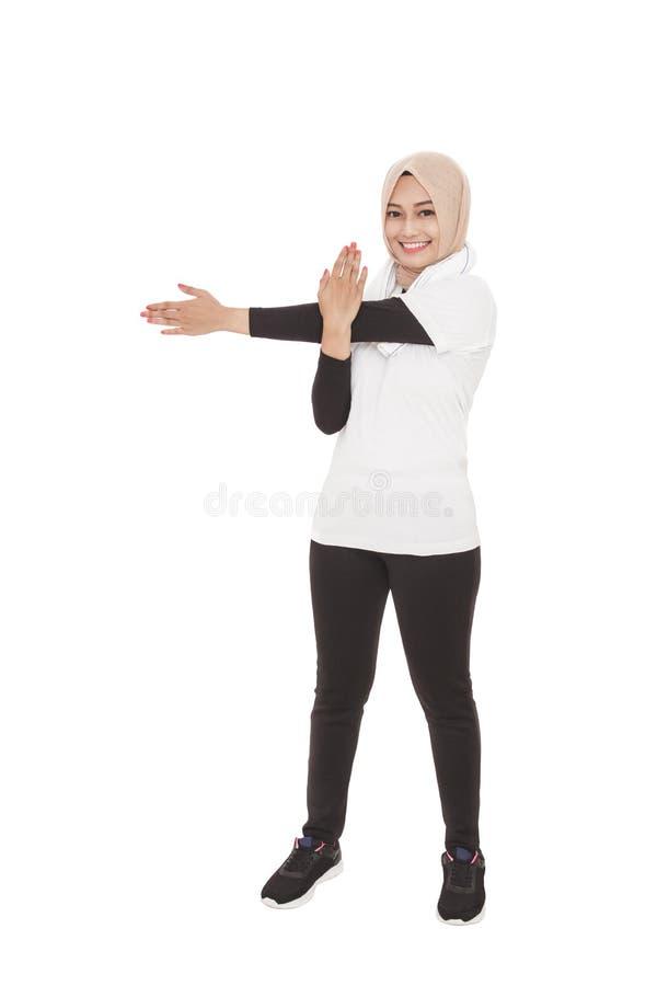 Mujer deportiva musulmán que hace la mano que estira mientras que sonríe imagen de archivo