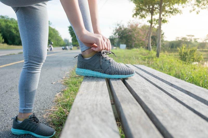 Mujer deportiva que ata el cordón en las zapatillas deportivas antes de práctica Concepto activo de la forma de vida del deporte foto de archivo libre de regalías