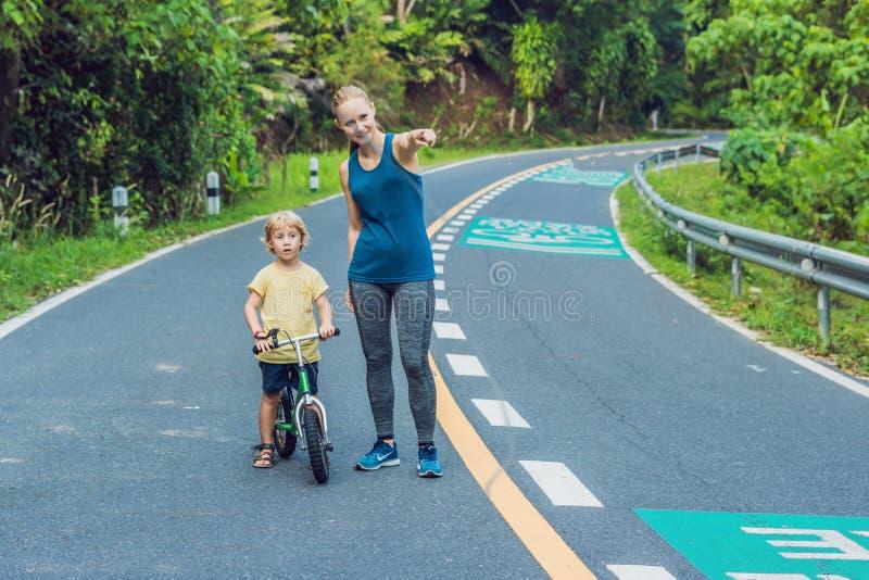 Mujer deportiva que corre en el camino en la salida del sol El hijo va a equilibrar la bici Concepto de la salud de la aptitud y  foto de archivo