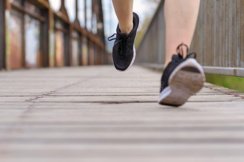 Mujer deportiva que corre en un puente viejo del paseo marítimo foto de archivo libre de regalías