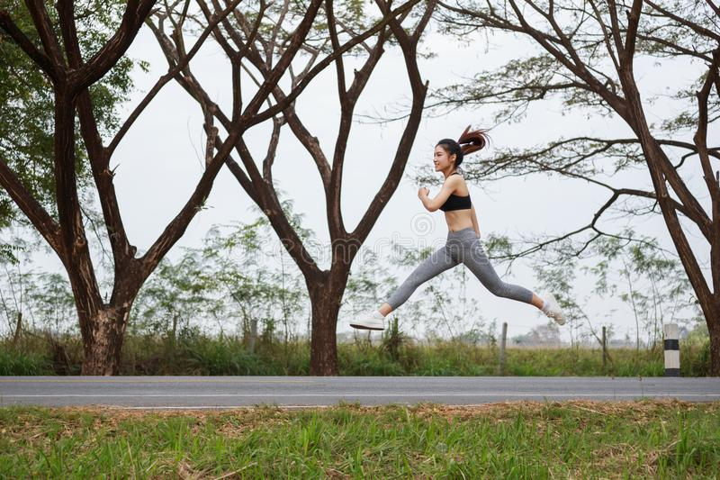 Mujer deportiva que corre y que salta en parque fotografía de archivo libre de regalías