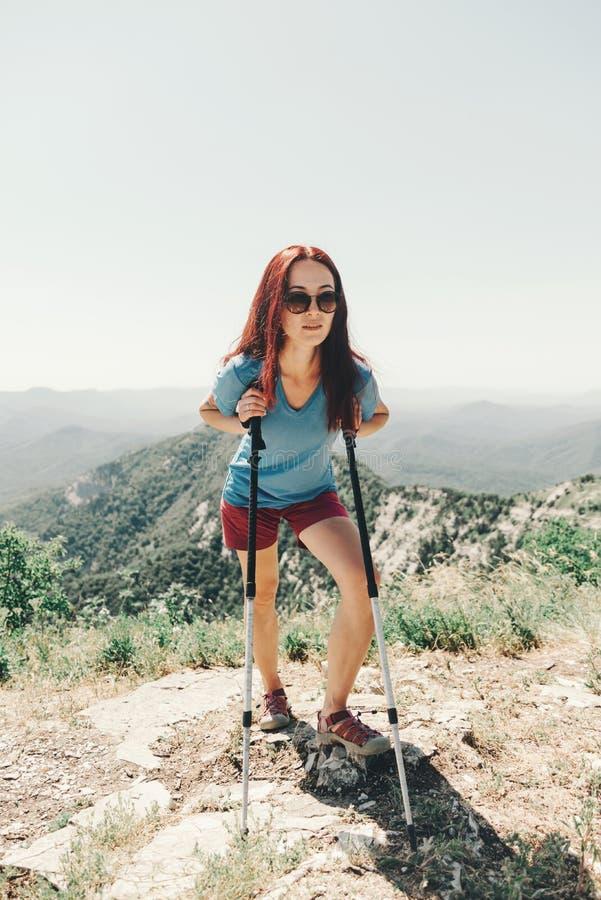 Mujer deportiva que descansa con emigrar polos en montañas foto de archivo libre de regalías