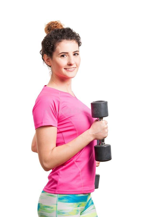 Mujer deportiva que ejercita con dos pesas de gimnasia negras imagen de archivo libre de regalías