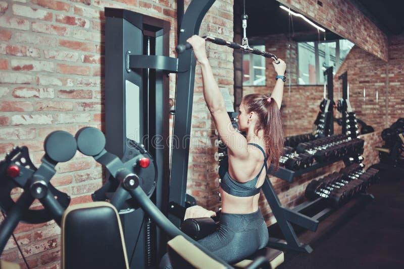 Mujer deportiva que entrena a su parte posterior con la máquina del peso en un gimnasio, concepto del deporte fotografía de archivo libre de regalías