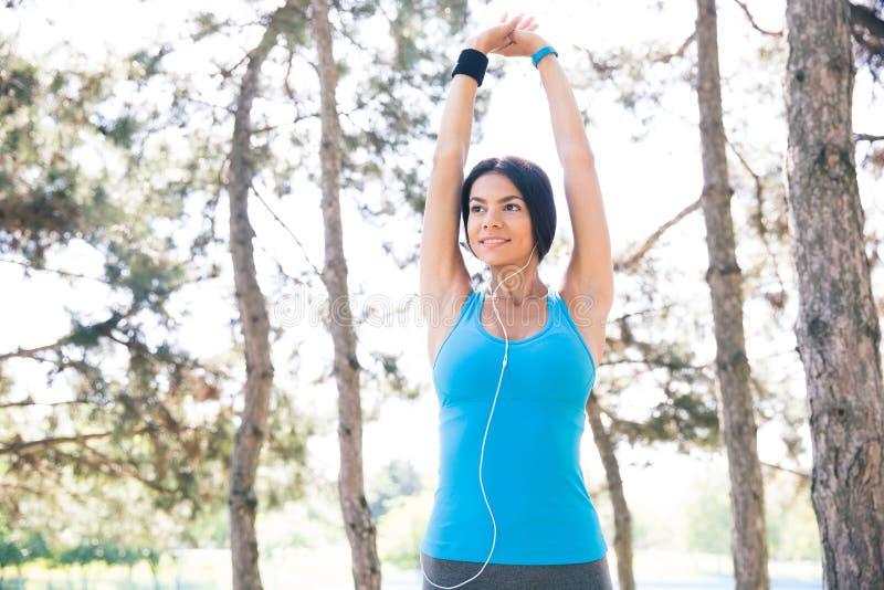 Mujer deportiva que estira las manos al aire libre fotos de archivo