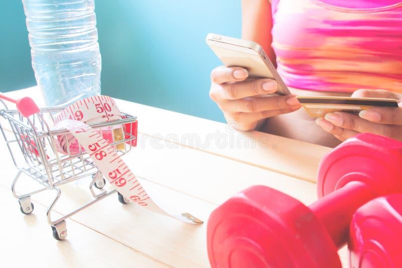 Mujer deportiva que hace compras en línea por el smartphone, forma de vida sana co fotos de archivo