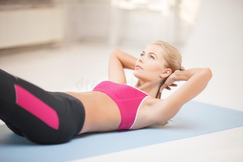 Mujer deportiva que hace ejercicio en el piso fotografía de archivo libre de regalías