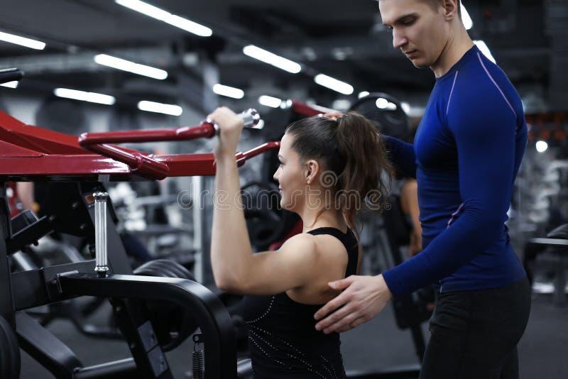 Mujer deportiva que hace ejercicios bajo supervisión de su instructor personal en gimnasio fotografía de archivo