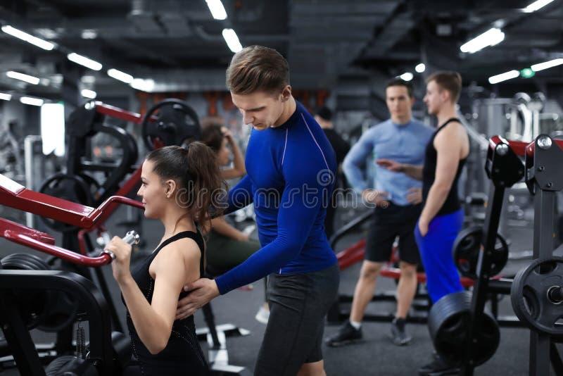 Mujer deportiva que hace ejercicios bajo supervisión de su instructor personal en gimnasio foto de archivo