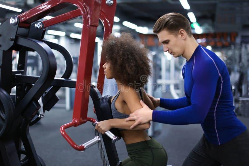 Mujer deportiva que hace ejercicios bajo supervisión de su instructor personal en gimnasio imágenes de archivo libres de regalías