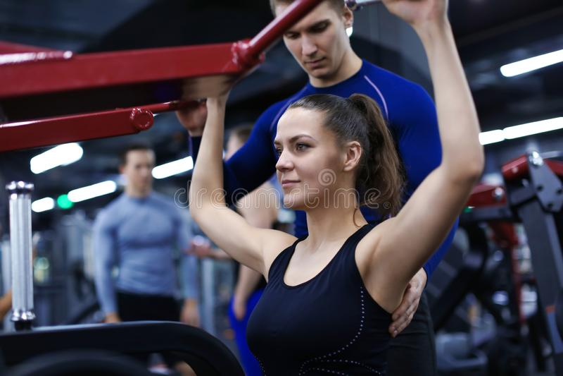 Mujer deportiva que hace ejercicios bajo supervisión de su instructor personal en gimnasio fotos de archivo