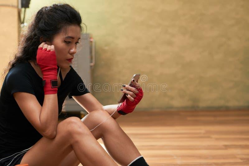 Mujer deportiva que manda un SMS imagen de archivo libre de regalías