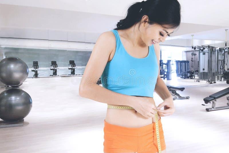 Mujer deportiva que mide su cintura delgada imagen de archivo libre de regalías