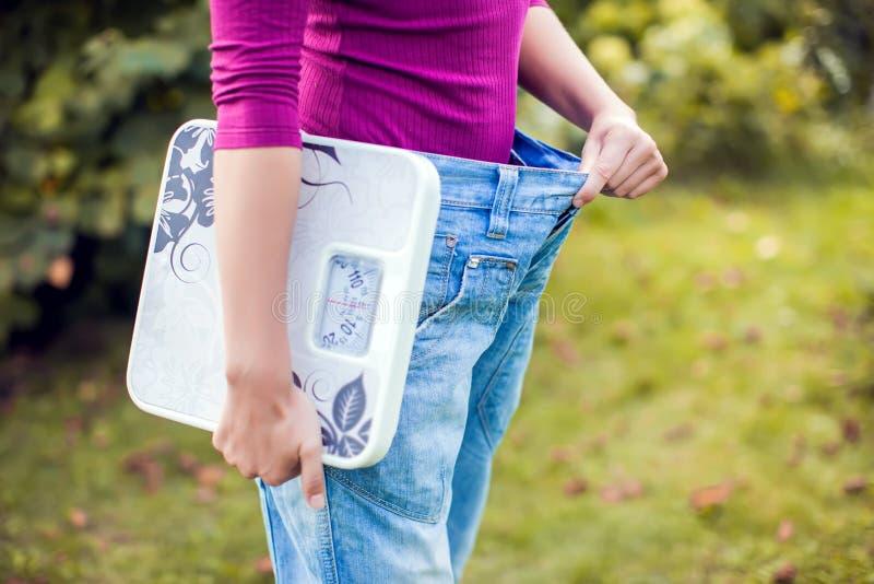 Mujer deportiva que muestra los pantalones grandes y que sostiene escalas Pérdida de peso c imágenes de archivo libres de regalías